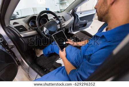 car service, repair, technology, maintenance and people concept - mechanic man with tablet pc computer making system diagnostic at workshop #629296352
