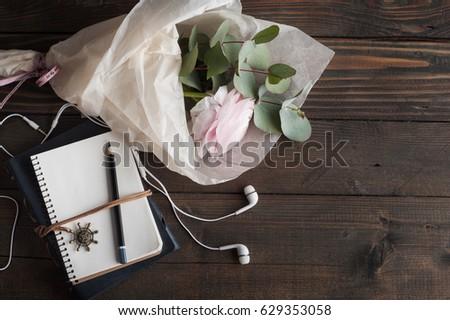 Pink ranunculus, open notebook, headphones on dark wooden background. Pastel colors, greeting card, toned vintage #629353058