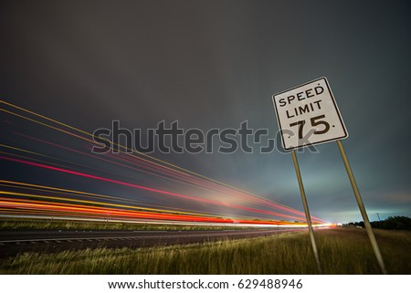 75np speed limit sign at night next to afreeway at night #629488946
