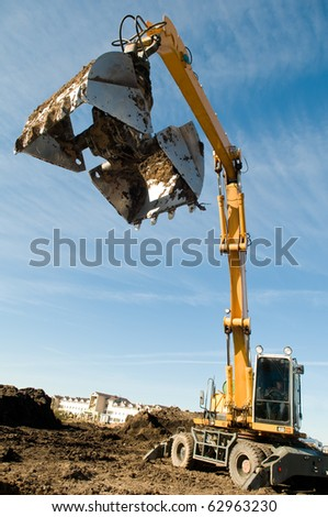 excavator loader machine during earthmoving works outdoors at construction site #62963230