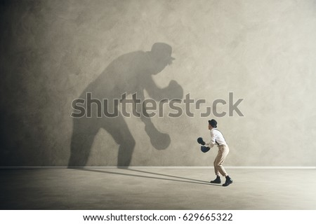 man fighting with his shadow, facing fears Royalty-Free Stock Photo #629665322