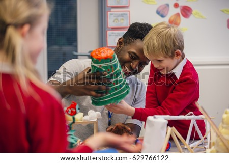 Young teacher is helping one of his primary school students during arts and crafts lesson.  Royalty-Free Stock Photo #629766122