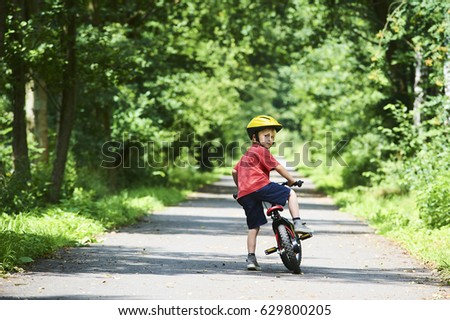 Young boy riding bicycle on a summer day at asphalt road. Bicycle path #629800205