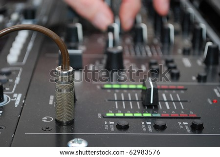 Royalty Free Stock Image of a photograph of a DJ's Headphone jack in the socket, taken close up with a shallow depth of field. A hand is seen in the background moving a slider.