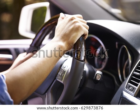hands of a male driver holding steering wheel of a vehicle, close-up. #629873876