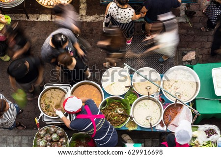 BANGKOK - DEC 16: Unidentified vendors serve food to customers at a streetside restaurant on Dec 16, 2016 in Bangkok, Thailand. Government figures indicate 20,000 registered street vendors in Bangkok. #629916698