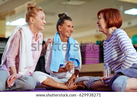 Friendly aged females drinking water and discussing workout at break #629938271