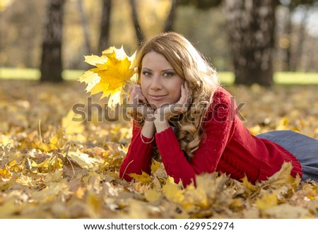 Beautiful girl in the autumn park #629952974