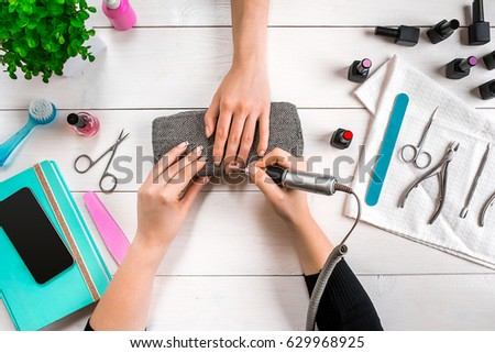 Nail care. Closeup of female hands filing nails with professional nail file in beauty nail salon. Top view #629968925