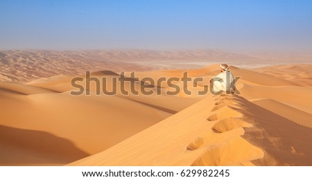 Arab man sitting on top of a dune in arabian desert #629982245