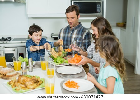 Smiling family having lunch together on dining table at home #630071477