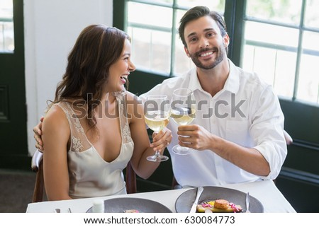Happy couple toasting wine glasses in the restaurant #630084773
