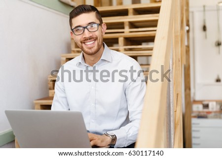 Portrait of young man sitting at the stairs in office #630117140