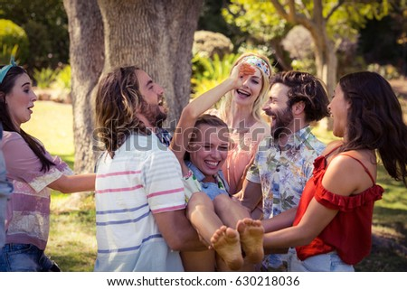 Group of friends lifting woman at campsite on a sunny day #630218036