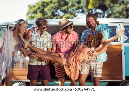 Group of friends lifting woman near campervan in park #630244991
