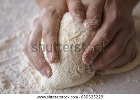 Close-up male hands kneading dough on sprinkled with flour table #630325229