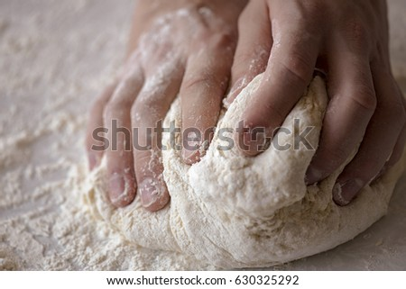 Close-up male hands kneading dough on sprinkled with flour table #630325292