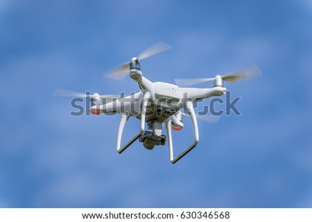 White drone hovering in a bright blue sky #630346568
