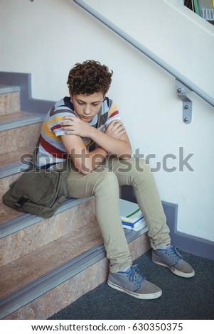 Sad schoolboy sitting alone on staircase in school #630350375