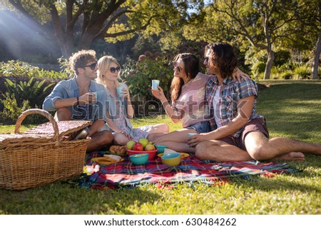 Happy friends having picnic in the park on a sunny day #630484262