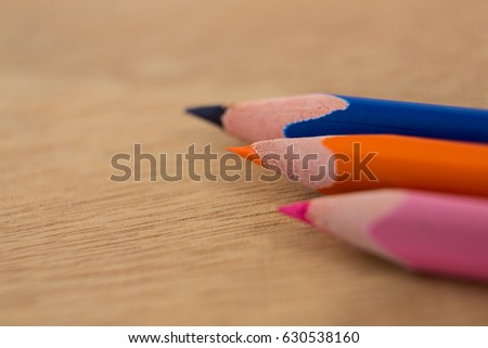 Close-up of colored pencils arranged in diagonal line on wooden background #630538160