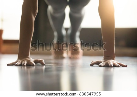 Young woman practicing yoga, doing Push ups or press ups exercise, phalankasana Plank pose, working out, wearing sportswear, grey pants, indoor, home interior, living room floor. Close-up of hands  Royalty-Free Stock Photo #630547955