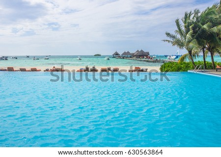 Blue swimming pool water and palm trees near the sea. Summer vacations in tropical resort. #630563864