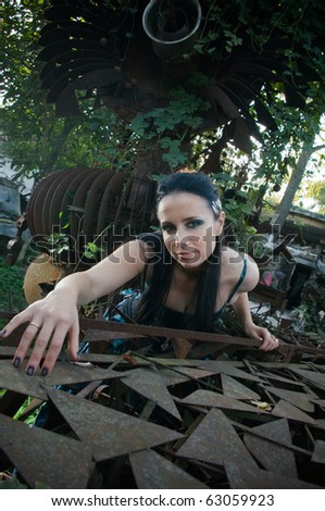 Woman wearing a designer industrial goth dress in an industrial setting #63059923