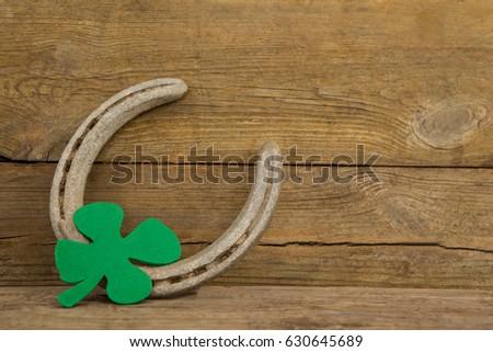 St Patricks Day shamrock with horseshoe on wooden surface #630645689