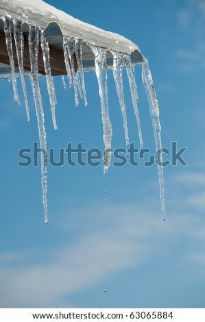 Thawing icicles with water drops falling against blue skies Royalty-Free Stock Photo #63065884