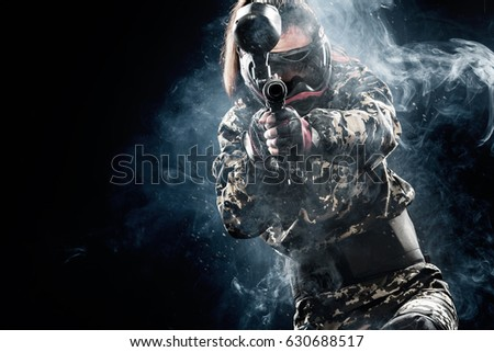 Heavily armed masked paintball soldier isolated on black background. Ad concept. #630688517