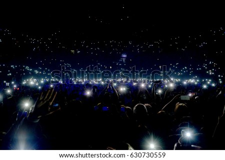 Crowd at concert with lights and camera flash on Royalty-Free Stock Photo #630730559