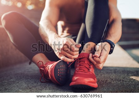 Man tying jogging shoes.A person running outdoors on a sunny day. Royalty-Free Stock Photo #630769961