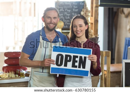 Portrait of smiling bakery staff holding board with open sign at counter in bake shop #630780155