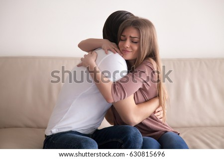 Portrait of emotional young couple hugging each other tightly, boyfriend and girlfriend embracing sitting on couch, reconciliation after argument, love you so much, strong affection in relationships #630815696