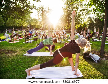 big group of adults attending a yoga class outside in park #630816977