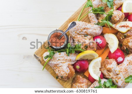Chicken wings are ready for baking, lemon slices, parsley sprigs, bright red radish, spices in a vintage carved pepper box with a small spoon on a wooden cutting board. #630819761