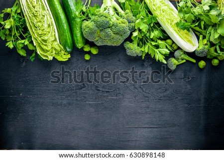Collection of fresh green vegetables placed on black stone #630898148