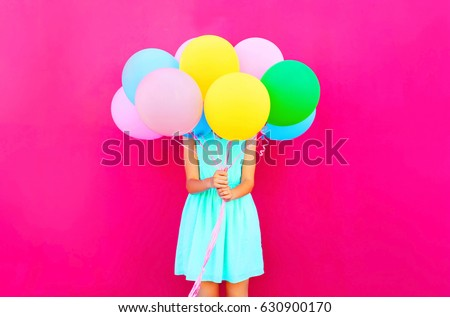 Woman is hides her head an air colorful balloons having fun over pink background #630900170