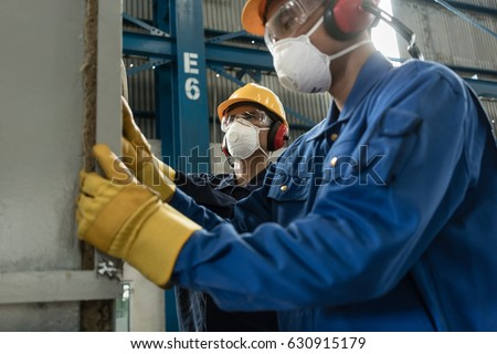 Two blue-collar workers wearing protective equipment while insulating an industrial pressure vessel #630915179