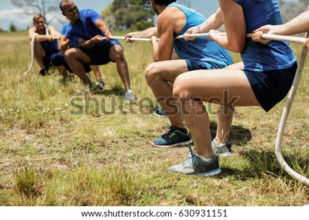 People playing tug of war during obstacle training course in boot camp Royalty-Free Stock Photo #630931151