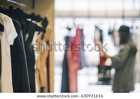 Shopping concept: girl in a boutique loonking at clothes. #630931616