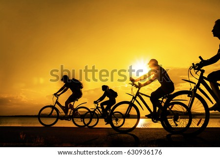 Image of sporty company friends on bicycles outdoors against sunset. Silhouette A lot phases of motion go of three 3 cyclist along shoreline coast. Reflection sun on water. Copy Space for inscription
