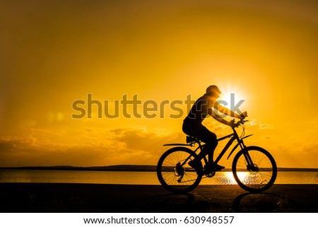 Image of sporty one tourist man walking along the shore with the bike against sunset sky with clouds and sun rays. alone woman Silhouette race with high speed #630948557