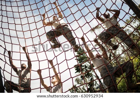 Military soldiers climbing rope during obstacle course in boot camp Royalty-Free Stock Photo #630952934