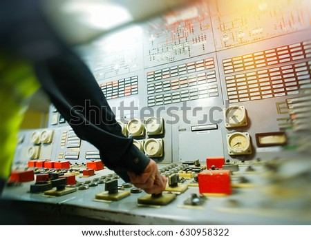 Hand on the control panel of a power plant           Royalty-Free Stock Photo #630958322