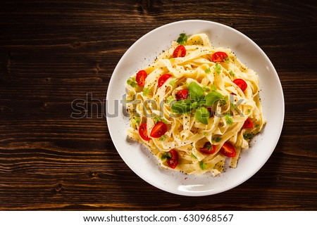 Pasta with tomatoes on wooden table  #630968567