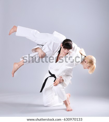 Young sporty women practicing martial arts on light background #630970133