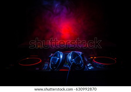 DJ Spinning, Mixing, and Scratching in a Night Club, Hands of dj tweak various track controls on dj's deck, strobe lights and fog, selective focus, close up Royalty-Free Stock Photo #630992870