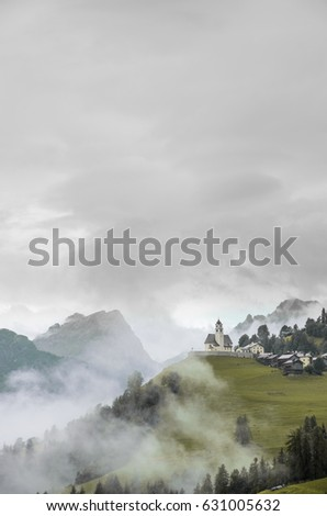 A foggy morning in Alps mountains, Colle Santa Lucia church in clouds and haze int the middle of high hills. Colored b&w picture